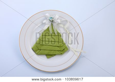 folded napkin to the shape of christmas tree with ribbon on top of plate