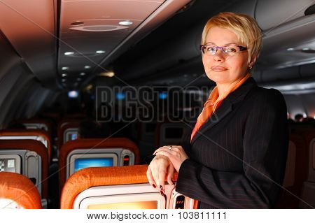 Business woman posing in modern jet aircraft