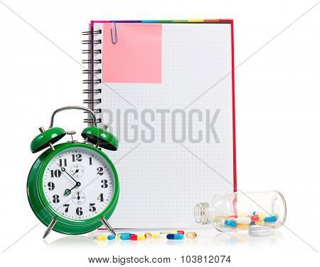 Big green alarm clock with blank notebook and pills, isolated on white background