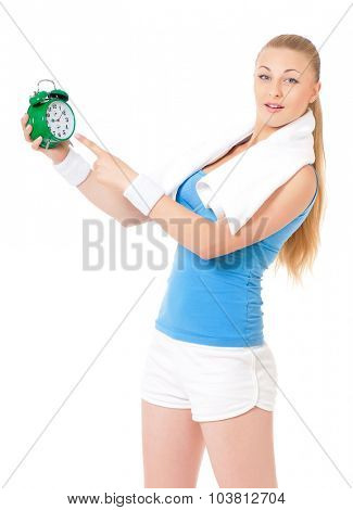 Young fitness woman with towel and green alarm clock, isolated on white background
