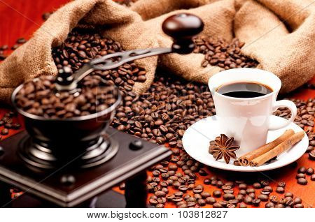 Coffee grinder and cup of coffee with spices on dark red background
