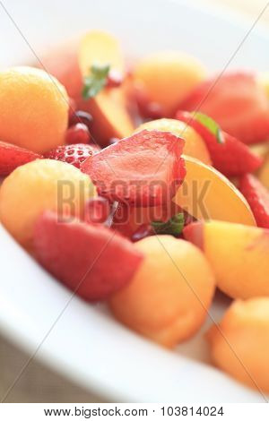 Peaches, strawberries, cantaloupe on white plate