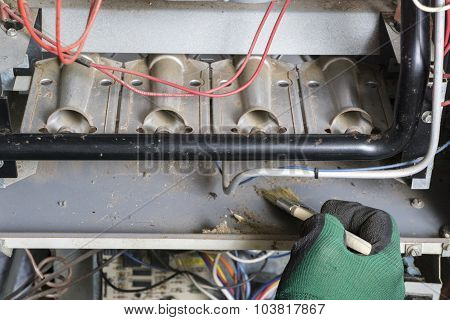 Technician Using Brush To Clean Under Burners