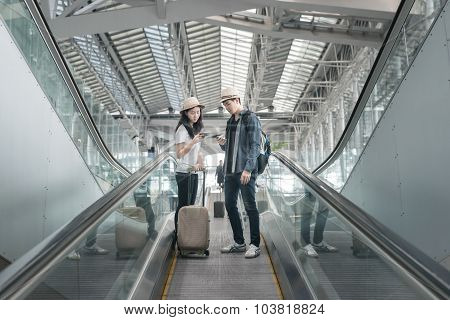 Young Asian Couple With Luggage Down The Escalator In Airport