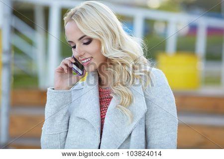 Beautiful girl talking on the phone on the street