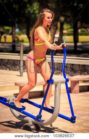 Closeup Blonde Girl In Bikini Trains On Stepper On Sport Ground