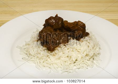 Lamb Vindaloo with rice on a white plate.