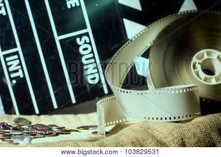Cinema Clapper And Video Film Negative Movie On A Rough Cloth.