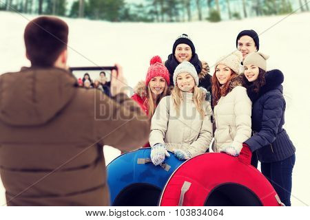 winter, leisure, sport, friendship and people concept - group of smiling friends with snow tubes taking picture by tablet pc computer outdoors