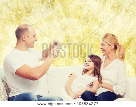 family, holidays, technology and people concept - smiling mother, father and little girl with camera over yellow lights background