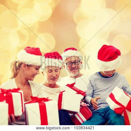 family, christmas, generation, holidays and people concept - happy family in santa helper hats with gift boxes sitting over beige lights background