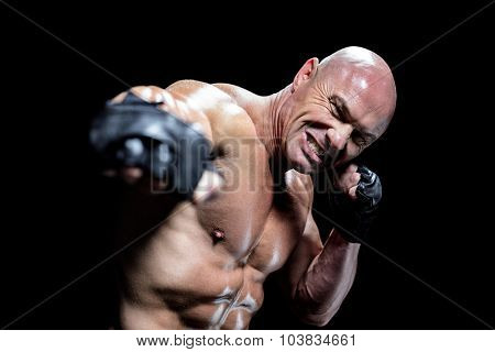 Portrait of aggressive fighter against black background