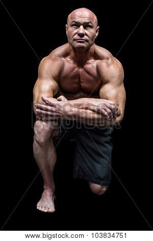 Muscular man kneeling down against black background