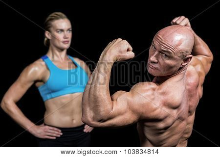 Muscular man flexing muscles in front of instructor against black background