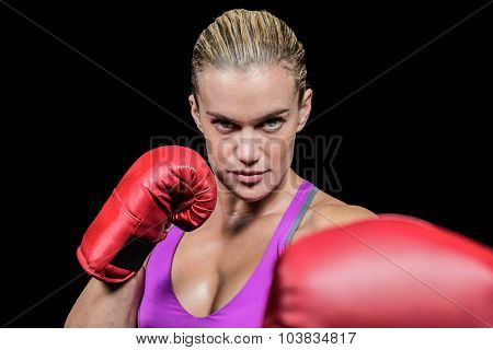 Portrait of female boxer with fighting stance against black background