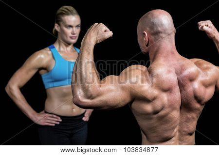 Bald muscular man flexing muscles in front of trainer against black background