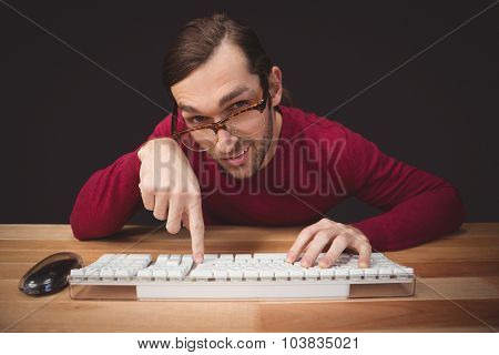 Portrait of man wearing eye glasses pointing on computer keyboard at desk in office