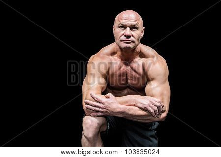 Muscular man flexing while kneeling against black background