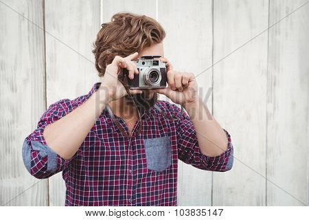 Hipster photographing with camera against wooden fence