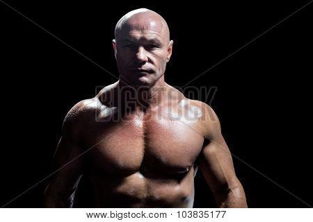 Portrait of confident fit man against black background