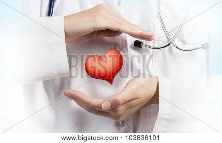 Close up of female doctor holding heart in hands