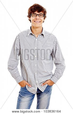 Young hispanic man wearing checkered shirt, blue jeans and black glasses standing with hands in pockets and smiling isolated on white background