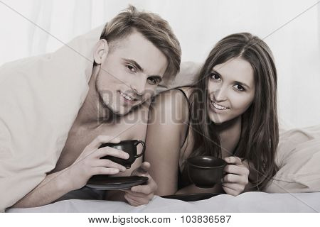 Young happy couple drinking coffee in bed.