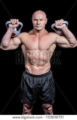 Portrait of muscular man lifting kettlebells against black background