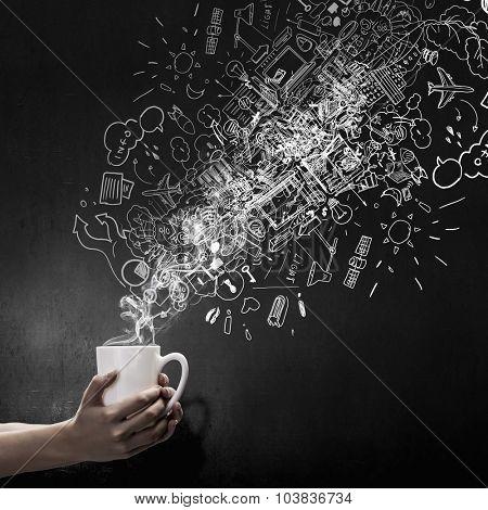 Close up of hand holding white mug of tea or coffee