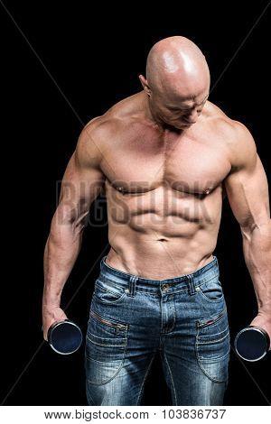 Bodybuilder exercising with dumbbells against black background