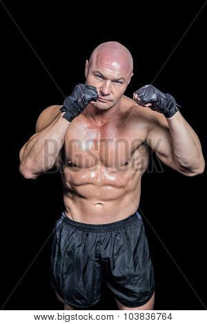 Portrait of bald muscular man against black background