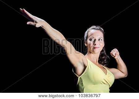 Beautiful athlete stretching hands against black background
