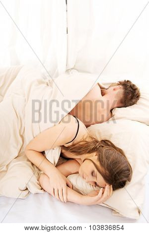 Young thoughtful woman and sleeping man in bed.