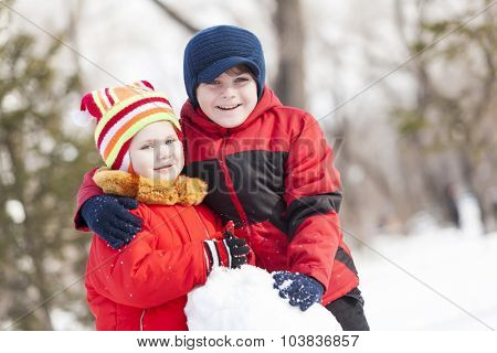 Cute boy and girl building snowman in winter park