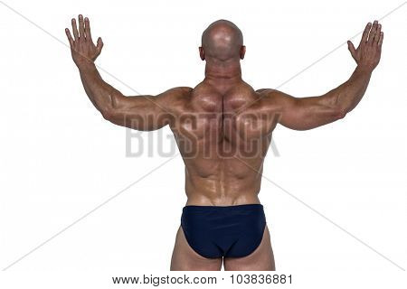 Rear view of muscular man with arms raised against white background