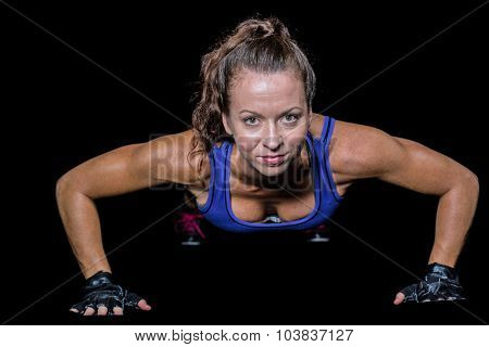Portrait of pretty woman doing push ups against black background