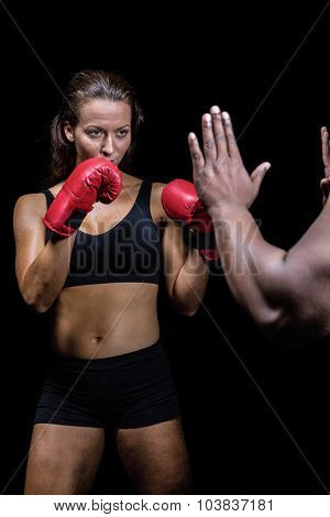 Female boxer with fighting stance against trainer hand over black background