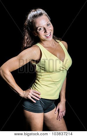 Portrait of happy athlete with hand on hip against black background