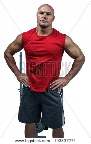 Portrait of bodybuilder with hands on hip against white background