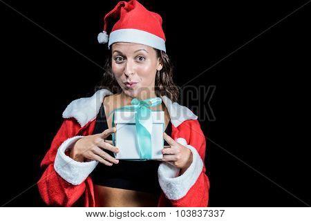 Portrait of athlete showing Christmas present against black background