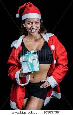 Portrait of female athlete holding Christmas gift with hand on hip against black background