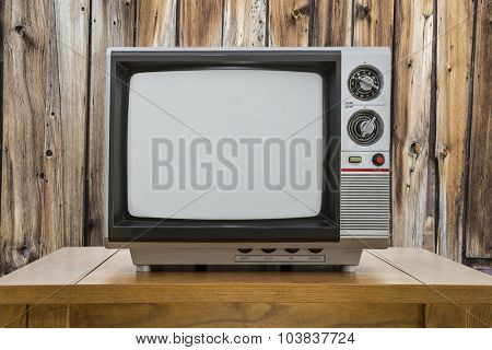 Vintage portable television and table with rustic cabin wall.