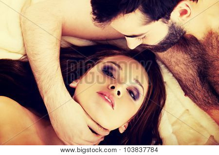 Relaxed loving young couple lying in bed.