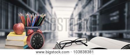 School supplies on desk against close up of a bookshelf