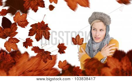 Attractive blonde wearing a warm hat against autumn leaves
