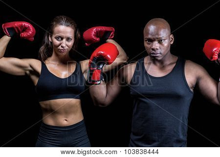 Portrait of boxers flexing muscles against black background