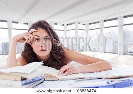 Bored student doing her homework against windows overlooking city