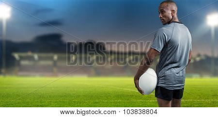 Rear view of confident athlete standing with rugby ball against pitch
