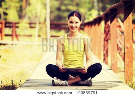 Beautiful woman surfing on tablet after running