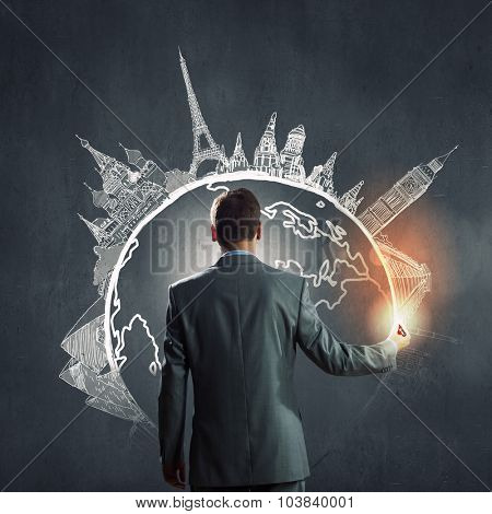 Back view of businessman drawing on wall concept of traveling